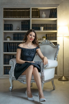 Een mooie vrouw met make-up en rode lippenstift zit in een zwarte jurk op een witte stoel tegen planken met boeken