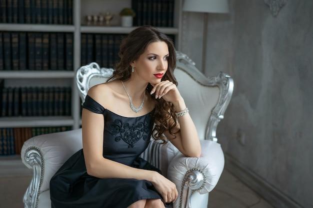 Een mooie vrouw met make-up en rode lippenstift zit in een zwarte jurk op een witte stoel