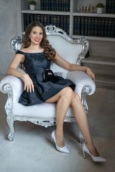 Een mooie vrouw met make-up en rode lippenstift zit in een zwarte jurk op witte stoel tegen planken met boeken