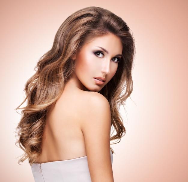 Een mooie vrouw met mooi lang golvend haar poseren op gekleurde achtergrond