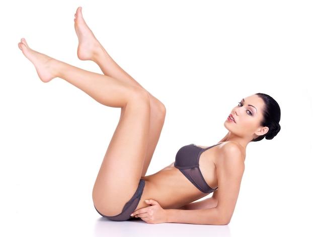 Een mooie vrouw met opgeheven lange benen die op wit worden geïsoleerd