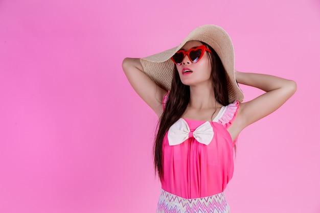 Een mooie vrouw met rode bril met een grote hoed op een roze.