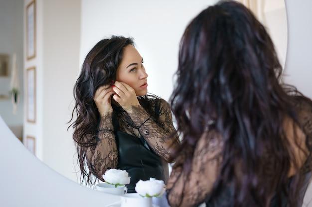 Een mooie vrouw met zwart haar en make-up staat voor de spiegel in een zwarte jurk, kijkt naar zichzelf in de reflectie en doet oorbellen aan