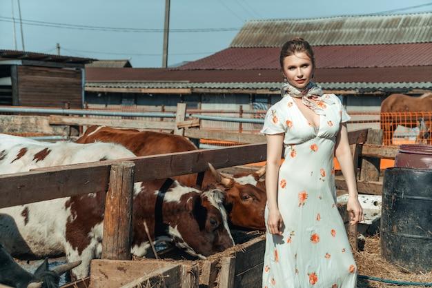 Een mooie vrouw op een boerderij voedt het vee met hooi