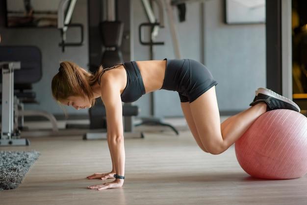 Een mooie vrouw op sportschool trainen met de bal voor het opbouwen van de spieren, concept van een gezonde levensstijl, sport, training, wellness en sport
