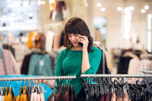 Een mooie vrouw praten over een telefoon, tijdens het winkelen in een winkelcentrum
