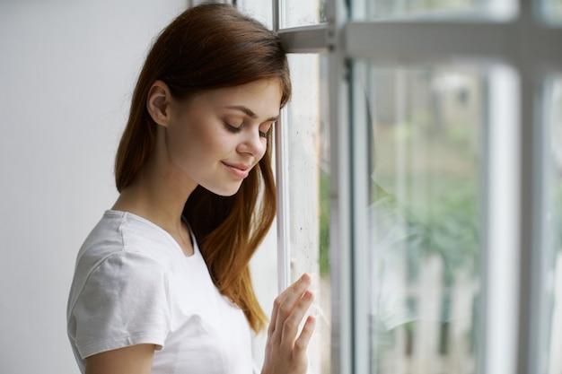 Een mooie vrouw raakt een raam in een gebouw aan