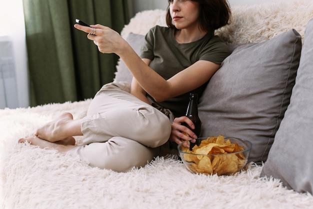 Een mooie vrouw schakelt kanalen op een tv