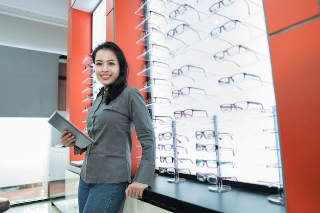 Een mooie vrouw toont een catalogus met beschikbare brillenproducten nadat ze een oogcontrole heeft ondergaan in een oogkliniek