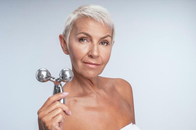 Een mooie vrouw van middelbare leeftijd die een metalen gezichtsroller tegen de camera houdt