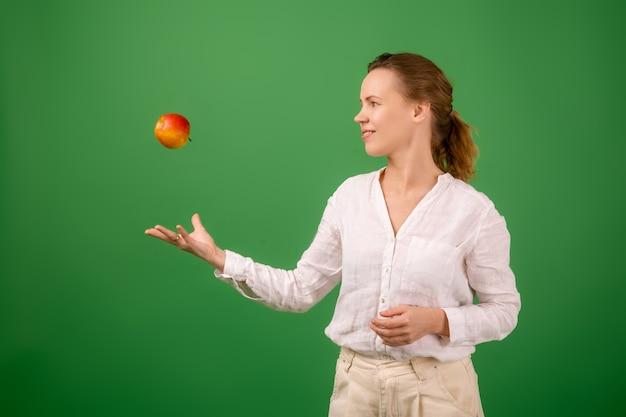 Een mooie vrouw van middelbare leeftijd in een wit overhemd gooit een verse appel op een groene achtergrond. het concept van gezonde voeding, vegetarisme.