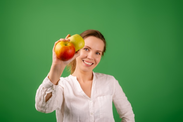 Een mooie vrouw van middelbare leeftijd in een wit overhemd toont appels op een groene achtergrond. het concept van voeding, gezonde voeding, vegetarisme.