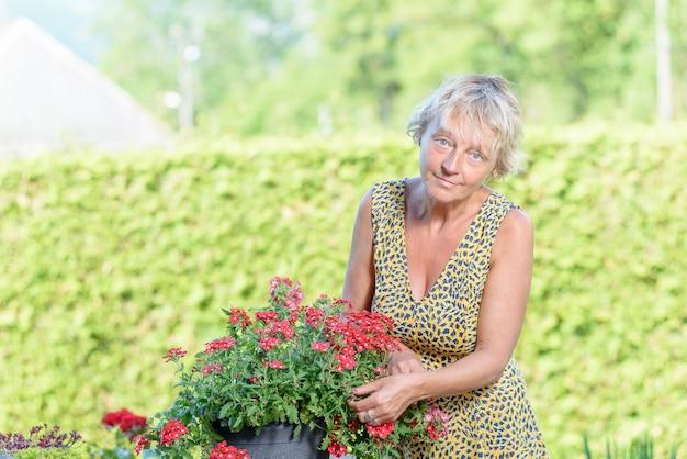 Een mooie vrouw van middelbare leeftijd zorg bloemen