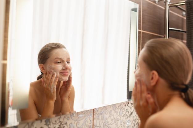 Een mooie vrouw wast haar huid op haar gezicht in de badkamer bij de spiegel en lacht