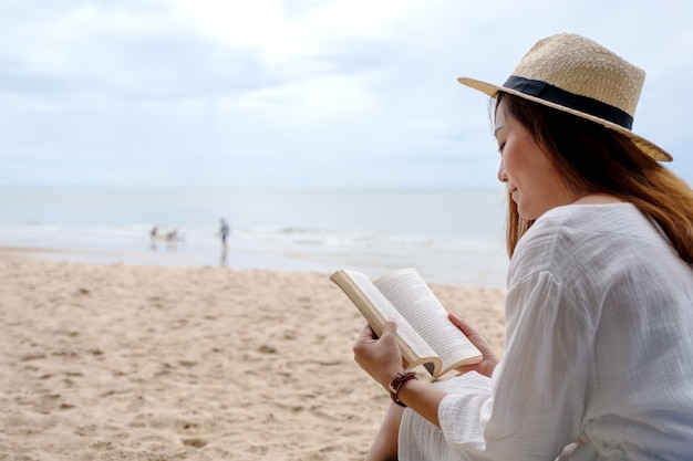 Een mooie vrouw zit en leest een boek op de strandstoel met een ontspannen gevoel