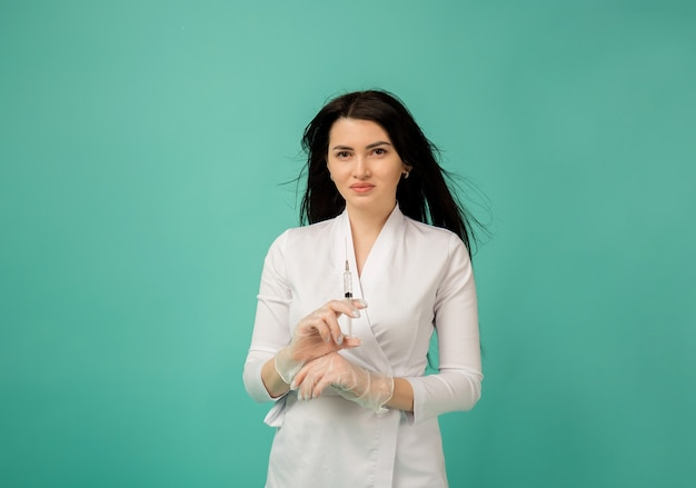 Een mooie vrouwelijke arts in een wit pak en transparante handschoenen houdt een spuit met medicijnen op turkoois