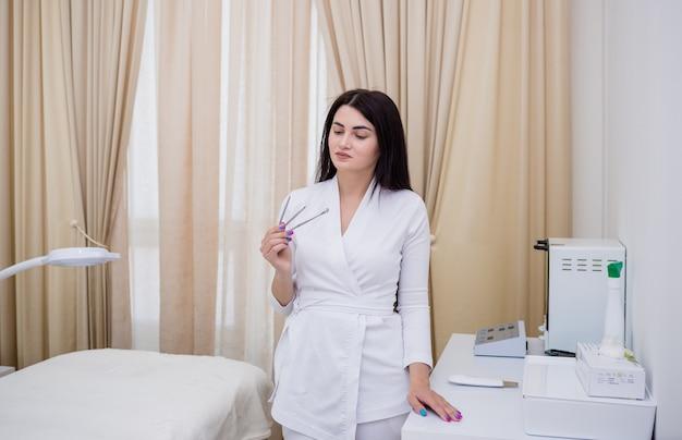 Een mooie vrouwelijke arts in een wit uniform houdt gereedschap vast