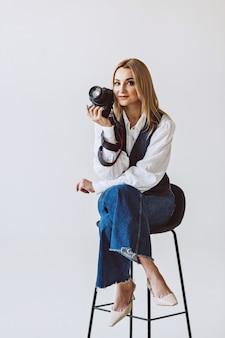 Een mooie vrouwelijke fotograaf in een casual denim outfit en een witte blouse met volumineuze mouwen met een camera in haar handen. hobby's. zachte selectieve aandacht.