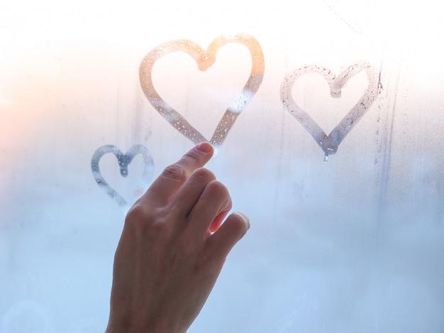 Een mooie vrouwelijke hand trekt een hart op een mistig raam. valentijnsdag concept.