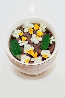 Een mooie witte kop met een gouden rand versierd met bloemen, kruiden groene gezonde thee. zakelijk account ontwerp.