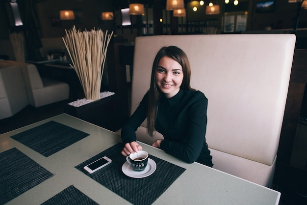 Een mooie zakelijke dame in een zwart shirt lachend in een café