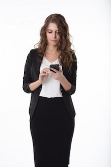 Een mooie zakenvrouw in een witte blouse en zwarte rok typt een bericht op haar mobiele telefoon