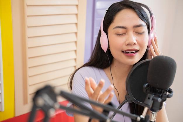 Een mooie zangeres die een koptelefoon draagt met handgebaren terwijl ze naar een nummer luistert