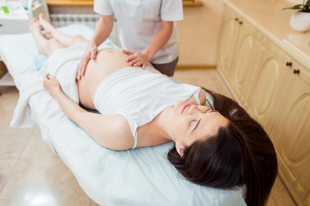 Een mooie zwangere brunette met lang haar ligt op haar zij bij een receptie met een massagetherapeut in een cosmetologie kamer