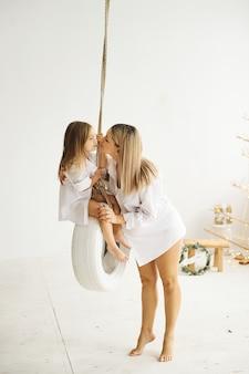 Een mooie zwangere moeder speelt met haar dochter op een schommel in een witte kamer