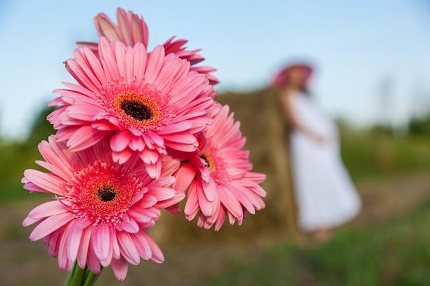 Een mooie zwangere vrouw in een roze hoed houdt handen op de buik op de achtergrond van een hooibaal.
