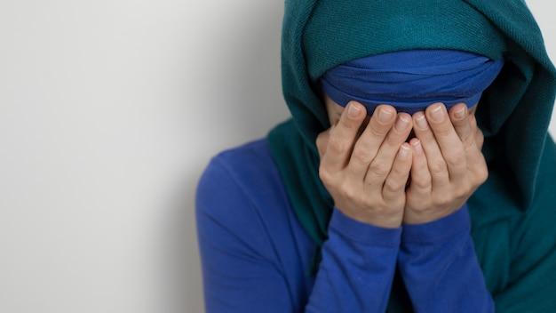 Een moslim in een hijab huilt met haar gezicht bedekt met haar handen
