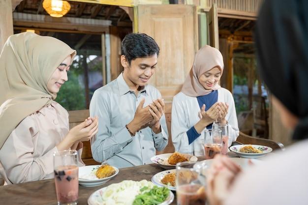Een moslimman en een gesluierde vrouw bidden samen voor het eten