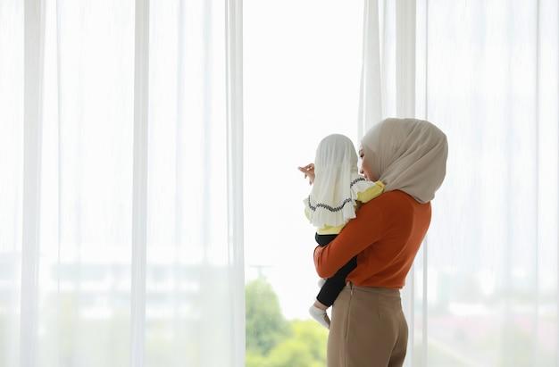 Een moslimmoeder en peuter zijn binnen in hun slaapkamer. de moeder draagt een hoofddoek