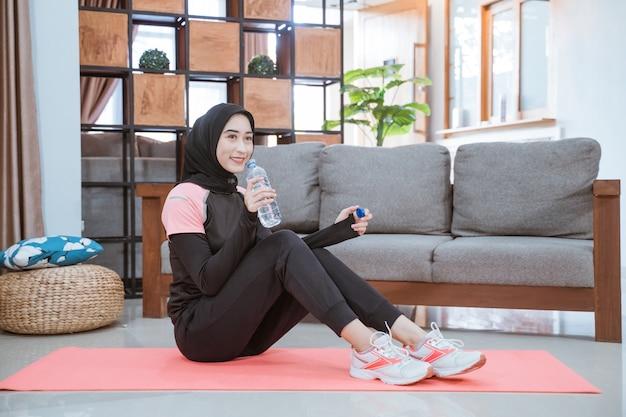 Een moslimvrouw die een hijab-gymkleding draagt, zit op de grond met een drinkwaterfles in de woonkamer