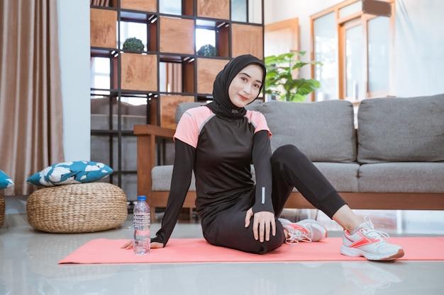 Een moslimvrouw die een hijab-gymkleding draagt, zit thuis nonchalant bij een waterfles op de grond