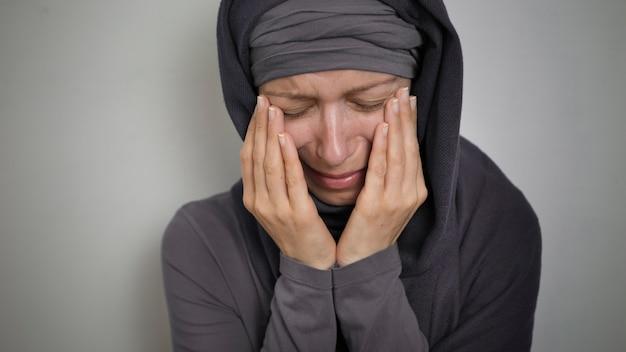 Een moslimvrouw in een hijab huilt en bedekt haar gezicht met haar handen.