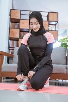 Een moslimvrouw in haar sportkleding hurkt en doet haar schoenveters vast terwijl ze thuis traint