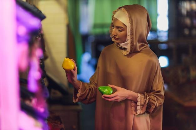 Een moslimvrouw in hijab die boodschappen koopt bij de supermarkt in het winkelcentrum.