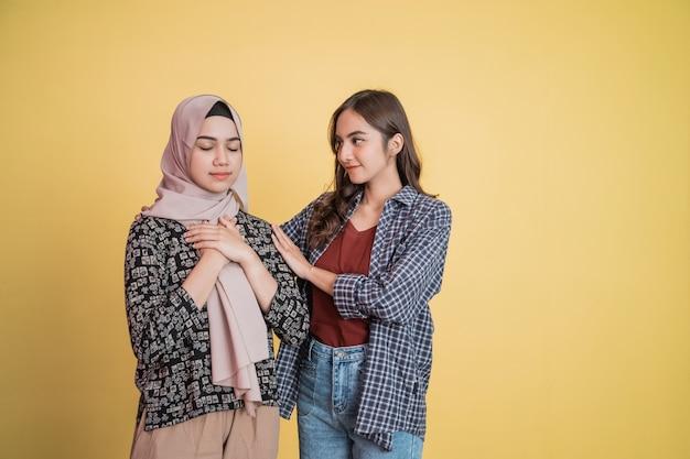 Een moslimvrouw met een paniekerig gebaar en een vriend die haar kalmeert