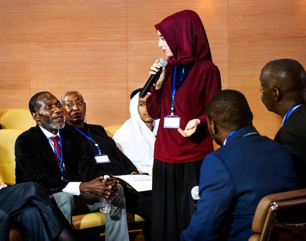 Een moslimvrouw spreekt in een microfoon in een groep zakelijke afgevaardigden