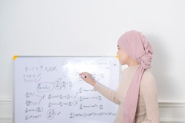 Een moslimvrouwendocent die laptop gebruikt om online via internet les te geven. e-learning en telecommunicatieconcept