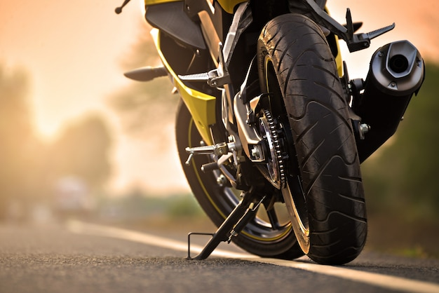 Een motorfietsparkeren op de juiste weg van de weg en zonsondergang