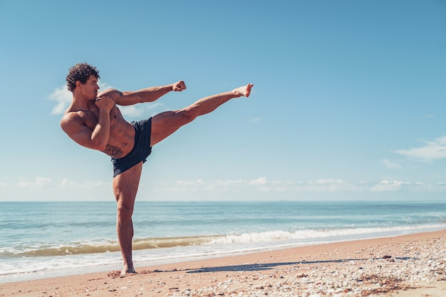 Een muay thai of kickbokser training met schaduwboksen buiten aan de kust