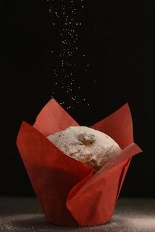 Een muffin in rood bakpapier staat op een tafel.