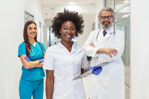Een multi-etnische groep van drie artsen en verpleegsters die in een ziekenhuisgang staan