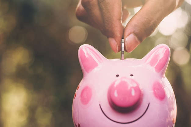 Een munt in de hand van een man die het in een roze spaarvarken zet.