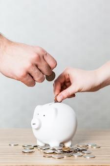 Een munt in een spaarvarken steken