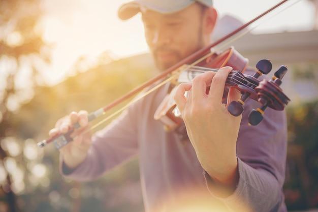 Een musicusman oefent de viool die geselecteerde nadruk speelt