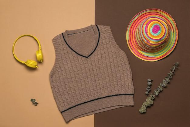 Een muts, een gebreid vest en een koptelefoon op een tweekleurige achtergrond.