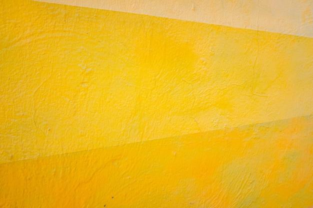 Een muur beschilderd met lijnen van verschillende kleuren, gele en oranje tinten.